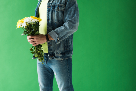 Cropped view of stylish mixed race man holding flowers on green screen with copy space Stock Photo