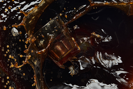Overturned glass with black coffee, big splash and drops