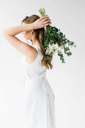 Young woman in dress holding flowers behind back isolated on white background