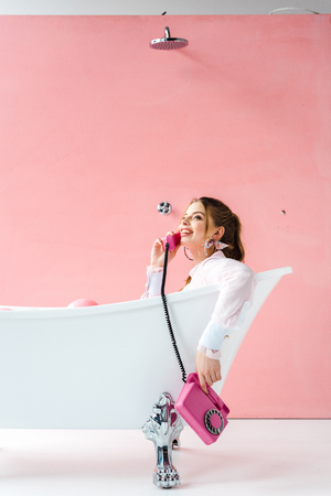 Happy girl talking on retro phone while lying in bathtub on pink background