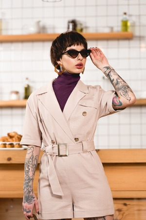 Beautiful businesswoman in sunglasses standing in cafeteria