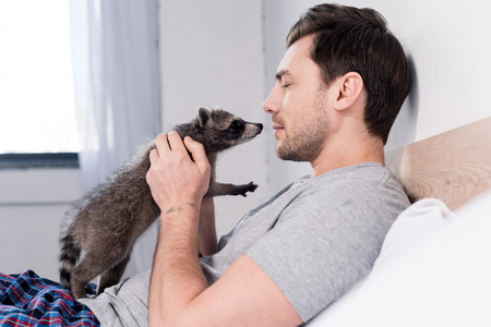 Handsome man cuddling with funny raccoon in bedroom at home
