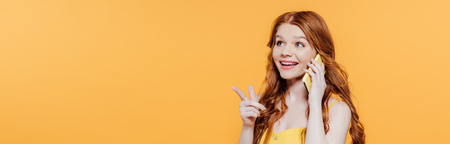Panoramic shot of beautiful smiling redhead girl pointing with finger while talking on smartphone