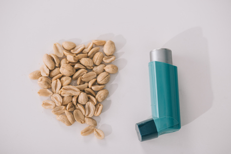 Top view of tasty nutritious peanuts near blue inhaler on grey background