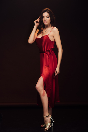 Beautiful sensual woman in red dress posing with eyes closed isolated on black background