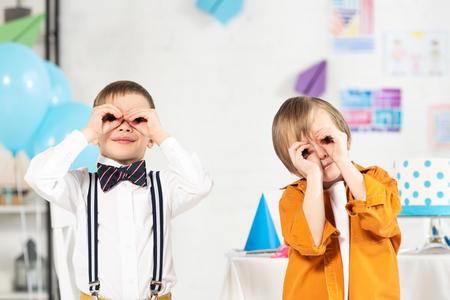 Adorable preteen boys looking at camera through fingers during birthday party Standard-Bild
