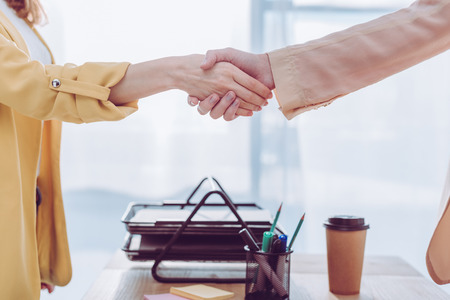 Cropped view of employee and recruiter shaking hands in office near paper cup Imagens - 120876041