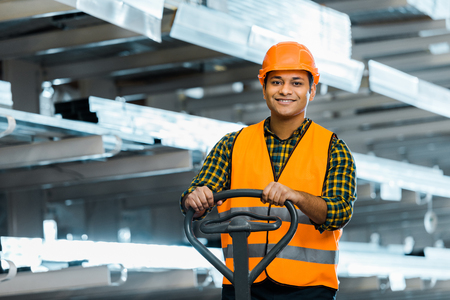 Smiling Indian warehouse worker standing near pallet jack, smiling and looking at camera