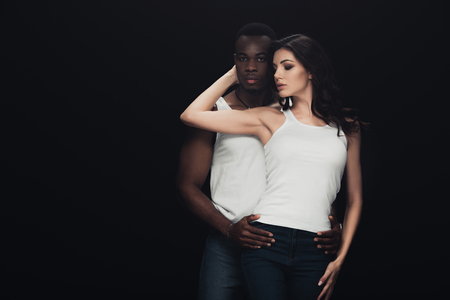 African american man embracing beautiful woman and looking at camera isolated on black with copy space 版權商用圖片