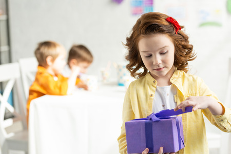 Selective focus of adorable kid opening present during birthday celebration