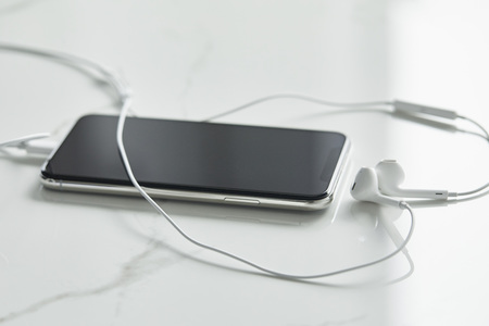 Selective focus of smartphone with blank screen and wired earphones on white surface Stok Fotoğraf
