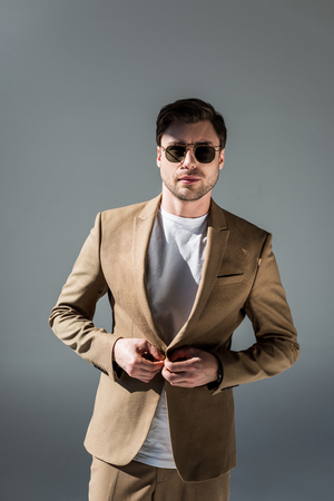 Handsome trendy man in beige suite and sunglasses looking at camera on grey background