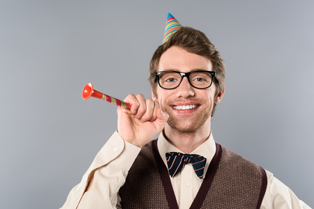 happy man in glasses and party cap holding party horn isolated on grey 免版税图像
