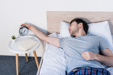 Handsome overslept man holding alarm clock while laying on bedding at home