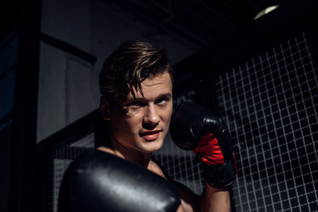 Handsome boxer in black boxing gloves training and looking away