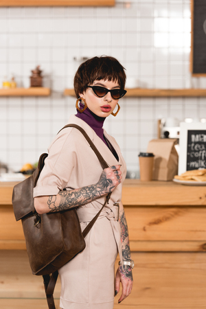Trendy, tattooed businesswoman in sunglasses standing in coffee shop and looking at camera Foto de archivo