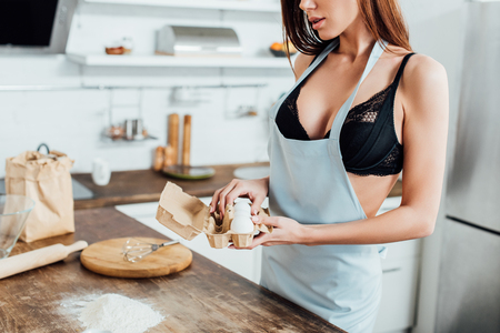 Cropped view of sexy woman in underwear and blue apron holding eggs in kitchen