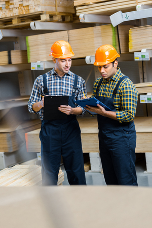Selective focus of two multicultural warehouse workers in uniform writing in clipboards