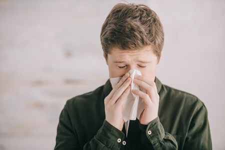 Man having allergy and sneezing in tissue at home