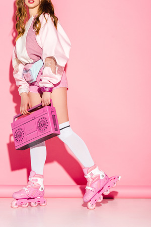 Cropped view of stylish girl holding retro boombox while standing in roller-skates on pink background Stock Photo