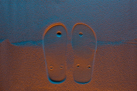 Top view of flip flops mark on sand with color filter