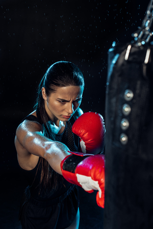 High angle view of pensive boxer in red boxing gloves training under water drops on black background