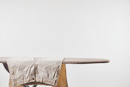 Beige male pants on ironing board isolated on grey