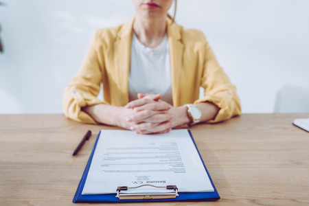 Selective focus of clipboard near recruiter sitting with clenched hands
