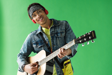 Handsome mixed race man in denim and headphones looking at camera while playing acoustic guitar on green screen background