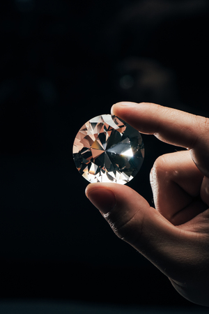Cropped view of man holding big clear shiny diamond on black background Stock Photo