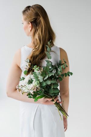 Back view of girl in elegant dress holding flowers behind back isolated on white background Reklamní fotografie