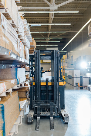 Forklift machine in warehouse near racks with wooden construction materials