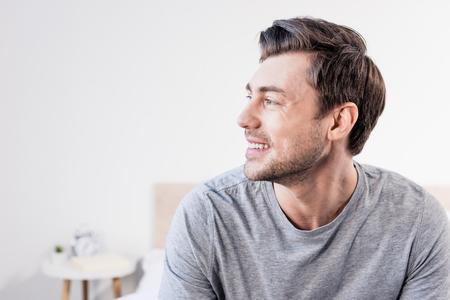 Hombre guapo en camiseta gris sonriendo y mirando a otro lado en casa Foto de archivo