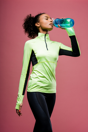 Beautiful African american sportswoman drinking water from sport bottle isolated on brown