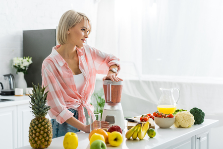 Dreamy young woman preparing delicious smoothie in blender