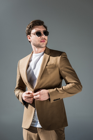 Confident trendy man in beige suite and sunglasses looking away on grey background