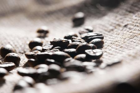 Selective focus of roasted coffee grains on sackcloth texture Reklamní fotografie