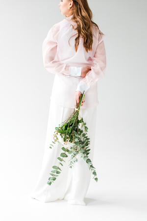 Cropped view of young woman holding bouquet of flowers with green eucalyptus leaves behind back on white background