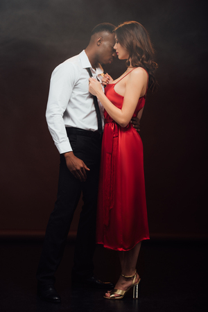 Beautiful woman in red dress undressing shirt of African american man isolated on black background
