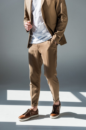 Partial view of trendy man in beige suite standing in sunlight on grey background 写真素材