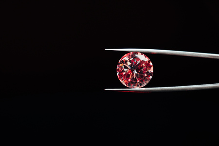 Colorful red sparkling diamond in tweezers isolated on black background