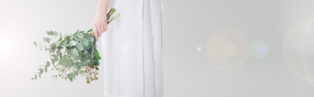 Panoramic shot of girl in dress holding flowers on white background