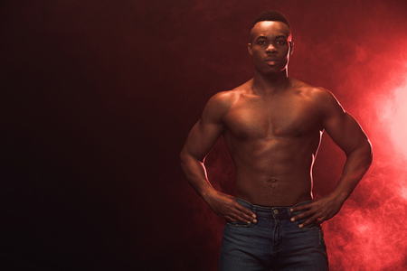 Sexy muscular African american man in denim looking at camera on dark with red light and copy space Stock Photo