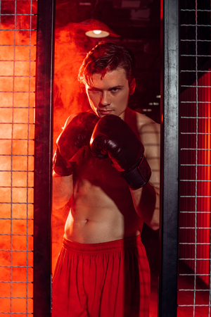 Handsome boxer in boxing gloves standing near wire netting and looking at camera Stok Fotoğraf