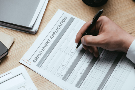 Cropped view of man filling in Employment Application Agreement Form Concept