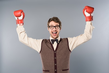 Happy man in glasses and boxing gloves rejoicing on grey background Banco de Imagens