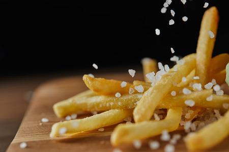 Nahaufnahme von Salz, das auf frische goldene Pommes frites auf Schneidebrett aus Holz fällt Standard-Bild