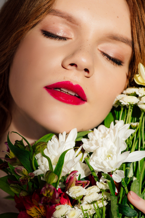 Close up of beautiful young redhead woman with red lips and eyes closed posing with flowers 版權商用圖片