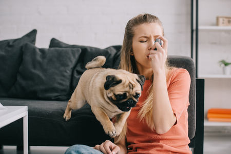 Beautiful blonde woman allergic to dog using inhaler near pug at home