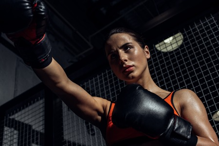 Low angle view of boxer in boxing gloves training and looking away